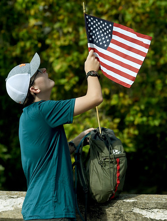 """Twelve-year-old Scout Josiah Starr, of Carl Junction's Troop 70, attaches a U.S. flag to his ruck sack before the start of the """"Let's Roll '19 Ruck March"""" on Saturday at Redings Mill Bridge. The event, sponsored by Compass Quest, included about 30 participants who hiked the 14-mile course to raise awareness concerning veteran's issues.<br /> Globe 