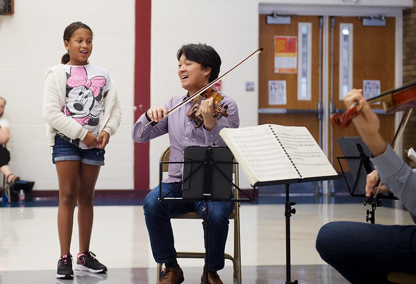 Daniel Ching helps Jannesa Praylow, fifth grader at Cecil Floyd, listen for the melody during a presentation on Wednesday.<br /> Globe | Roger Nomer