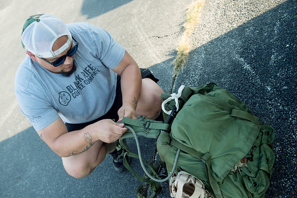 Enrique Medina prepares his ruck sack for a hike on Monday at the Frisco Greenway Trail.<br /> Globe | Roger Nomer