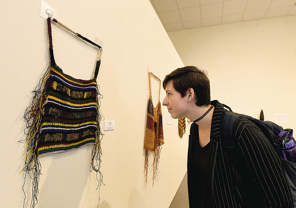 Missouri Southern freshman Erina Bragg checks out a bilum bag - a handmade bag made of string from plant fibers - during the Oceanic Journey: The Art of Papau New Guinea exhibit on Friday at MSSU's Spiva Art Gallery. Items on display are on loan from the Spurlock Museum at the University of Illinois - Urbana Champaign.<br /> Globe | Laurie Sisk