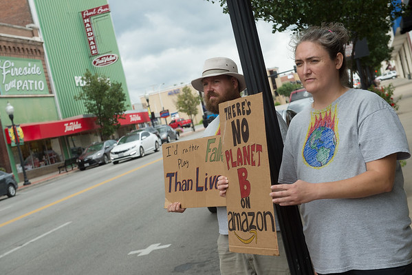 Kyle Perrin and Jen Gilbert, both from Sarcoxie, hold signs during Friday's local climate strike at Joplin City Hall.<br /> Globe   Roger Nomer