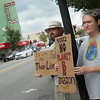Kyle Perrin and Jen Gilbert, both from Sarcoxie, hold signs during Friday's local climate strike at Joplin City Hall.<br /> Globe | Roger Nomer