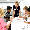 Kansas City University student Blair Freed assists West Central students as they try to piece together the anatomy of a human body during KCU's Score 1 for Health event on Tuesday at KCU. The children's preventative screening program involved about 130 West Central Elementary students and included basic health screenings and educational presentations for the kids. From the left: Seven-year-olds Carie Badgerow, Kayden Brown, Levi DeRose and lianna Grant.<br /> Globe | Laurie Sisk<br /> Globe | Laurie Sisk