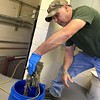 HEATHER BELLOW — THE BERKSHIRE EAGLE<br /> Wastewater department employee Lee Soules holds up congealed wipes<br /> that workers removed from a pump downstairs.