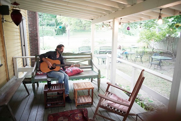 "BEN GARVER — THE BERKSHIRE EAGLE<br /> Adam Paulen of Brooklyn plays the ""house"" guitar at the Shaker Dam Coffee House in West Stockbridge in the outdoor space at the venue.  Customers can just use the guitar to relax, and if they are good, like Paulen is, the other guests can enjoy the music. Tuesday, August 13, 2019."