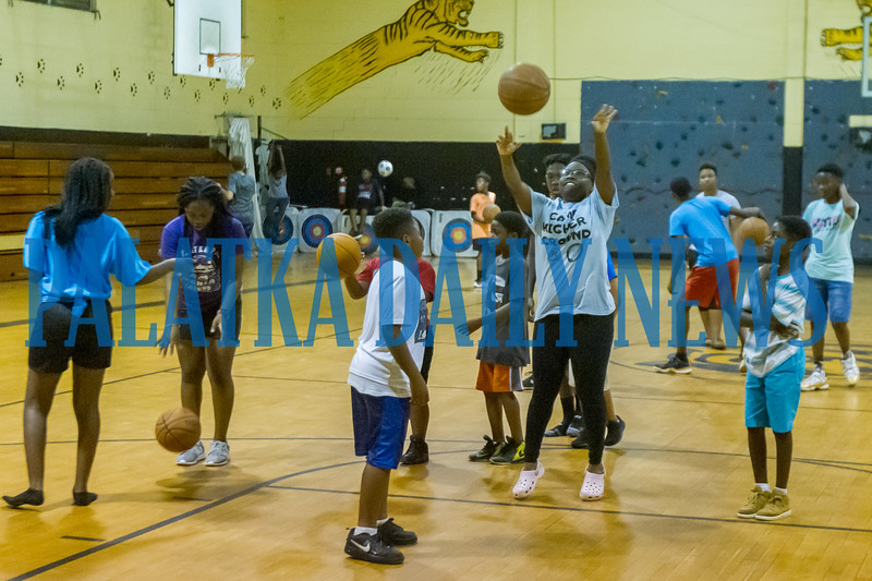Counselor Zaria Long, 16, center shows some of the older campers her basketball moves as they play basketball together at Camp Higher Ground on Tuesday afternoon. Fran Ruchalski/Palatka Daily News