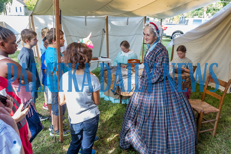 Jean Dominguez of the Golden Teacups tells visiting fourth-graders about life for women in 1864 at Occupation Palatka on Friday morning as Terri Blocker and Lauren Aponte, 12, sew behind her. Fran Ruchalski/Palatka Daily News