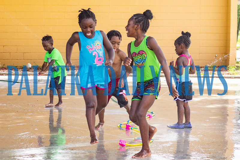 Children at D & G Childcare and Learning Center cool off on Friday morning by running through water sprinklers in the center's yard. Fran Ruchalski/Palatka Daily News