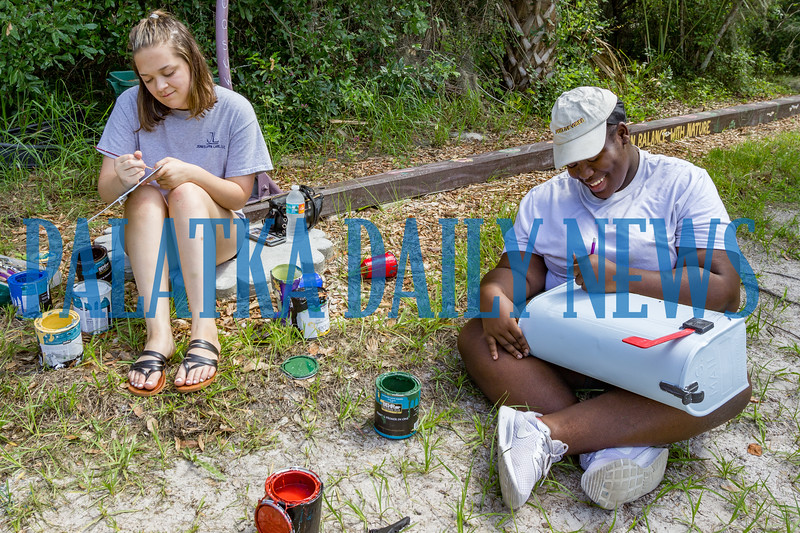 Q. I. Roberts art students Ashley Delarosa, 17, left, works on a sign and Tamecia Epps, 17, draws out a scene on the new mailbox for the Palatka Water Works on Tuesday morning. Fran Ruchalski/Palatka Daily News