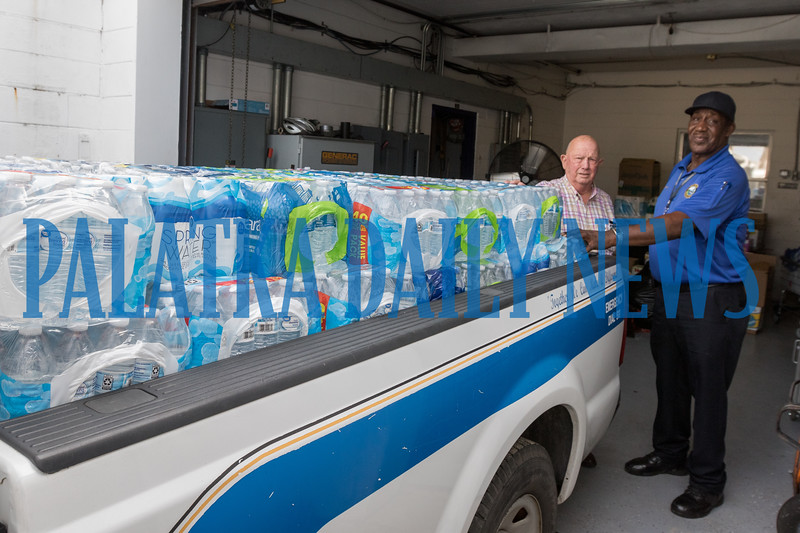 Interim City Manager Lee Garner and police maintenance employee Bobby Conyers take a break after this police pickup was completely loaded with cases of water headed for the Bahamas. Fran Ruchalski/Palatka Daily News