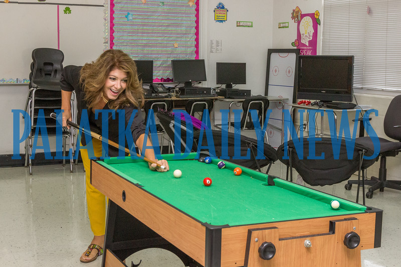 Principal Mary Brown gets off a shot on the mini pool table in the new student lounge installed near the cafeteria to reward student good behavior. The room also has gaming areas, fussball, and air hockey for the students to play. Fran Ruchalski/Palataka Daily News