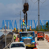 Workers attach the cables from the overhead cranes to one of the concrete I-beams to be put in place on the new SR 17 bridge over Dunn's Creek that is under construction. Fran Ruchalski/Palatka Daily News