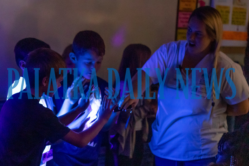 SJRSC nursing student Courtney Smith uses a black light to show students the presence of germs on their hands. Fran Ruchalski/Palatka Daily News