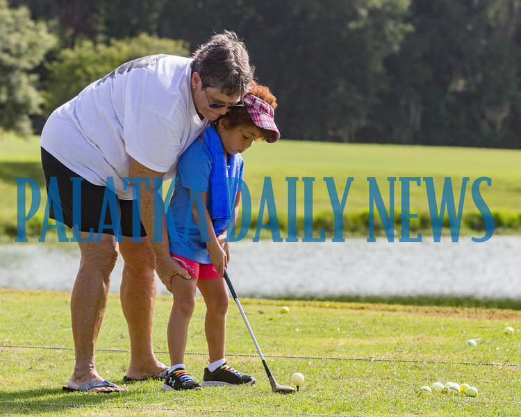 Holly Harris tries to help Avery Charles, 5, as she learns to tee off on the driving range at the Palatka Golf Club on Tuesday morning. Fran Ruchalski/Palatka Daily News