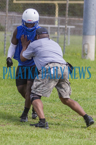 Coach Leeroy Jackson demonstrates the moves he wants his defensive backs to make on Thomas Mack during the first preseason practice at Interlachen High on Monday morning. Fran Ruchalski/Palatka Daily News
