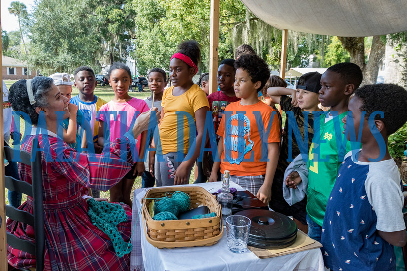 Asela Hopkins of the Golden Teacups demonstrates how knitting was done in 1864 with a needle made from a cow bone for students visiting Occupation Palatka on Friday morning. Fran Ruchalski/Palatka Daily News