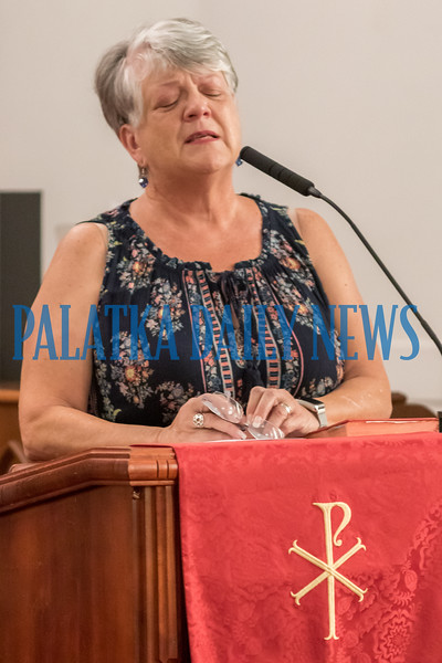 Minister Sophia Smith prays tearfully for the firefighters and first responders to have the strength to meet the challenges of their work. Fran Ruchalski/Palatka Daily News