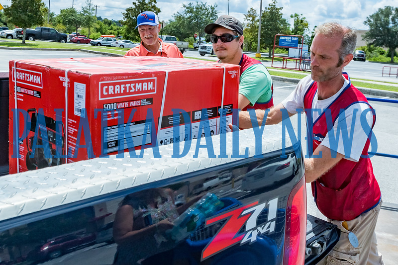 Ed McAuley, right, and Trey Davis load a generator into Rick Glover's truck Wednesday morning. Glover bought the last one Lowe's had in stock, but more are being brought down from Georgia. Fran Ruchalski/Palatka Daily News