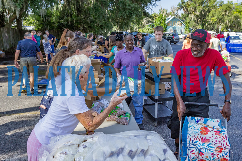 Volunteers load up people in need with a variety of food at the Community Food Bank on Thursday morning in the First Baptist Church parking lot. Fran Ruchalski/Palatka Daily News