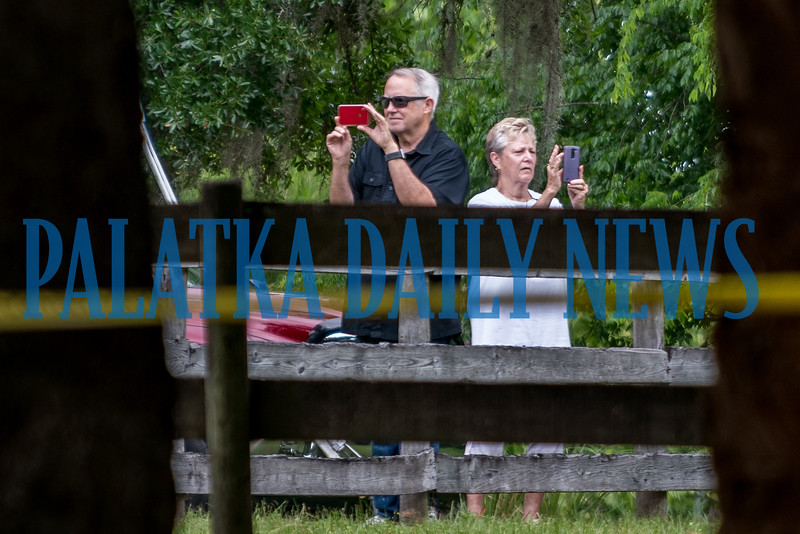 Neighbors stand outside the property of the reported suspect making videos and photos with their cellphones. Fran Ruchalski/Palatka Daily News