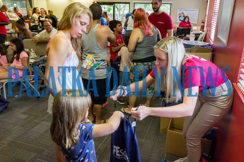 Life South intern Kelly Smith, right, gives out a backpack to a child at the first station at the Life South backpack giveaway on Friday morning. Fran Ruchalski/Palatka Daily News