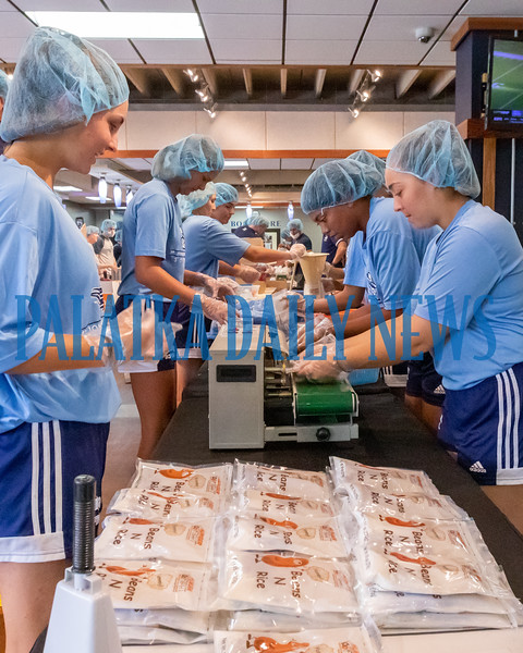 St. Johns River State College softball players pack beans and rice meals for the Feed the Need program in the Viking Center on Tuesday afternoon. Fran Ruchalski/Palatka Daily News