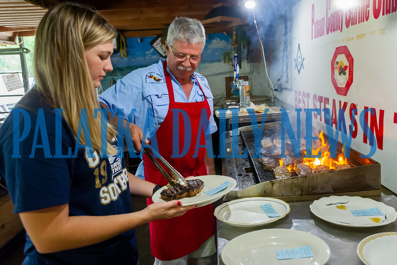 Payton Pellicer gets ready to deliver a steak that her dad, Walton Pellicer just took off the grill at the Putnam County Shrine Club on Friday night. Fran Ruchalski/Palatka Daily News