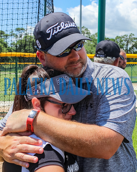 Peniel Baptist Academy's Kristen Flateau is consoled by her uncle, Rick, after the Warriors lost to Academy at the Lakes, 10-0, in five inning in the FHSAA 2A semifinals at the Jackie Robinson National Training Center in Vero Beach Tuesday. Mark Blumenthal/Palatka Daily News