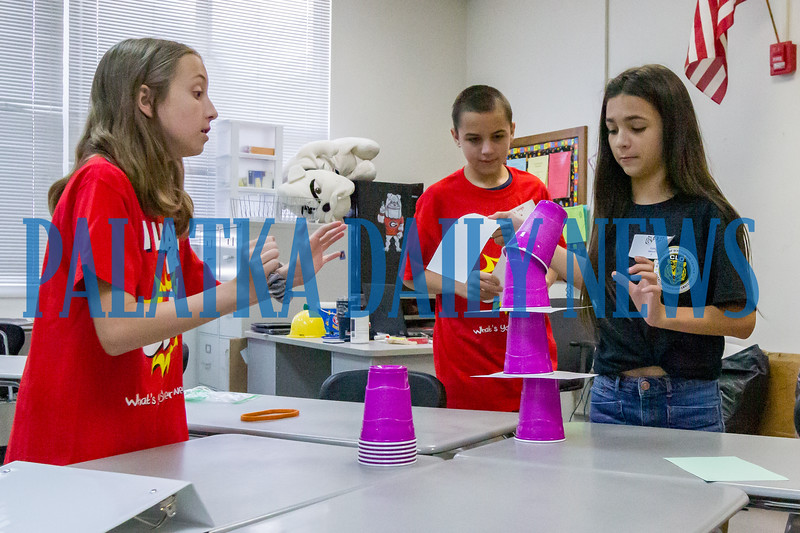 Kyie Mercer, 1, right, attempts to pull a piece of paper from a pile of cups while her teammates, Brooke Ward, 11, and Ty Lingle, 12, use body motions to help steady the pile during a team-building activity at C. L. Overturf as part of Camp Rise which familiarized the students with the facility and each other on Thursday morning. Fran Ruchalski/Palatka Daily News