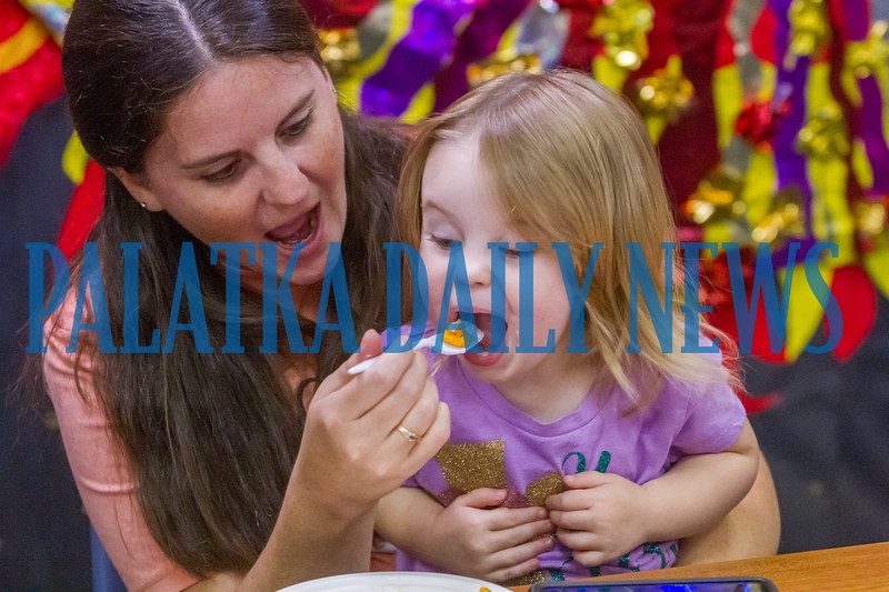 Two-year-old June Buckles can't wait to get another taste of the sweet potato fries and dip from her mom, Tami Buckles at the Palatka Library on Monday afternoon. Fran Ruchalski/Palatka Daily News