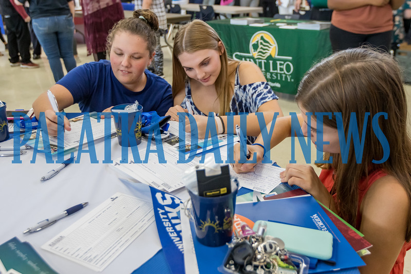 Marli Griffin, 16, from left, Emma Murrow, 16, and Kristen Godfrey, 16, fill out information cards for Keiser University at the career fair at Palatka High School Thursday night. Fran Ruchalski/Palatka Daily News
