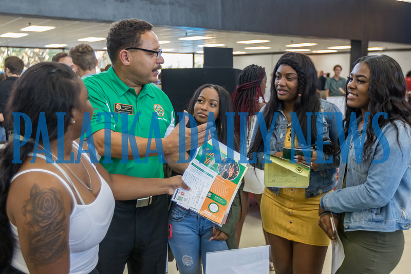 Les Ferrier of Florida A & M University talks about FAMU with Spenasia Cristopher, 18, from left, Tamia Bryson, 18, Destiny Lewis, 18, and Montalia Heath, 17, at the career fair at Palatka High School Thursday night. Fran Ruchalski/Palatka Daily News