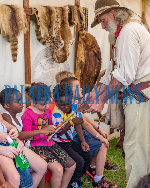 Robert Wilson as trading post proprietor Job Wiggins has students feel animal skins that he would have traded for at the Bartram Frolic learning experience for schoolchildren on Tuesday morning. Fran Ruchalski/Palatka Daily News