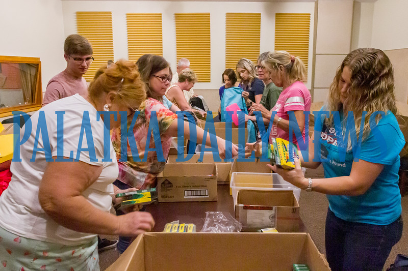 Staff and volunteers pack three hundred bookbags with a variety of school supplies that were donated by community members and local businesses. The bookbags will be delivered to Putnam County elementary schools so teachers can distribute them to children who don't have them. They will also be donating the extra supplies that were donated as well as socks and underwear to the schools for the kids that need them. Fran Ruchalski/Palatka Daily News