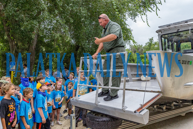 Putnam County Sheriffs Office school resource officer and marine unit deputy Joseph Abbott shows the daycampers at Camp Shands how the front of the marine unit becomes a ramp to load equipment on the boat. Fran Ruchalski/Palatka Daily News
