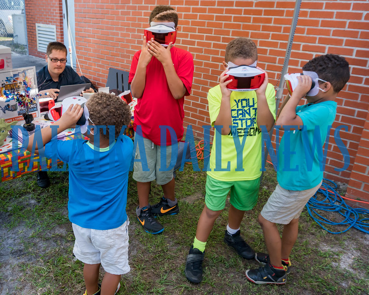 Zacharee Harvey, 6, from left, Noah Harvey, 9, Jonah Harvey, 8, and Blake Hayes, 7, use virtual reality goggles to put themselves into outer space at the library's exhibit at the PCSD STEM Carnival on Thursday afternoon.<br /> Zacharee Harvey, 6, uses virtual reality goggles to put himself into outer space at the PCSD STEM Carnival on Thursday afternoon. <br /> The Putnam County School District hosted the carnival at the PCSD Training Center where students demonstrated their projects with robots, drones, coding and software, competing for prizes in a friendly competition. The idea is to spark interest in Science, Technology, Engineering and Mathematics in kids, making the learning fun and preparing them for technology careers in the future. Fran Ruchalski/Palatka Daily News