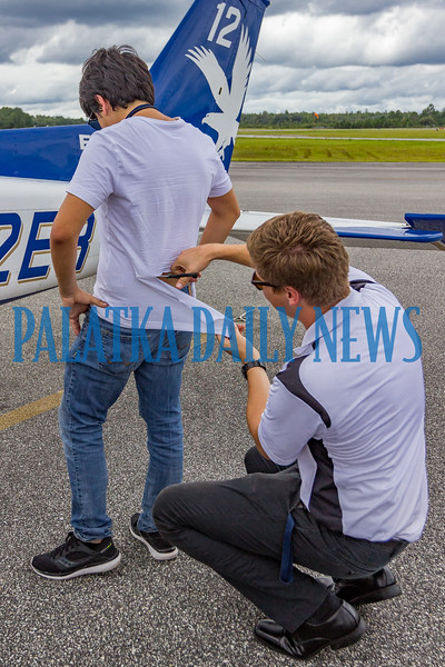 At the conclusion of his solo flight, Embrey-Riddle Flight Instructor Daniël Botes makes the traditional cut of the student's shirt. This signifies that an instructor can no longer grab the back of a student's shirt to tell him he's doing something wrong because he's proved himself to be a pilot. Fran Ruchalski/Palatka Daily News