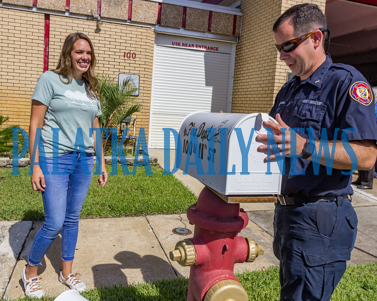 Jillian Spencer of Bannerville Oaks stands by as Firefighter Stephen Barker puts the new mailbox in place outside the firehouse on 11th Street on Monday morning. Fran Ruchalski/Palatka Daily News