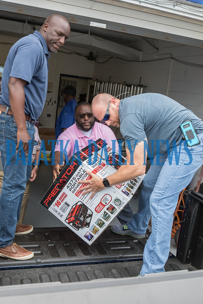 City Commissioners Rufus Borom, left, and Justin Campbell and Police Captain Matt Newcomb load a donated generator destined for the Bahamas onto a pickup truck. Fran Ruchalski/Palatka Daily News