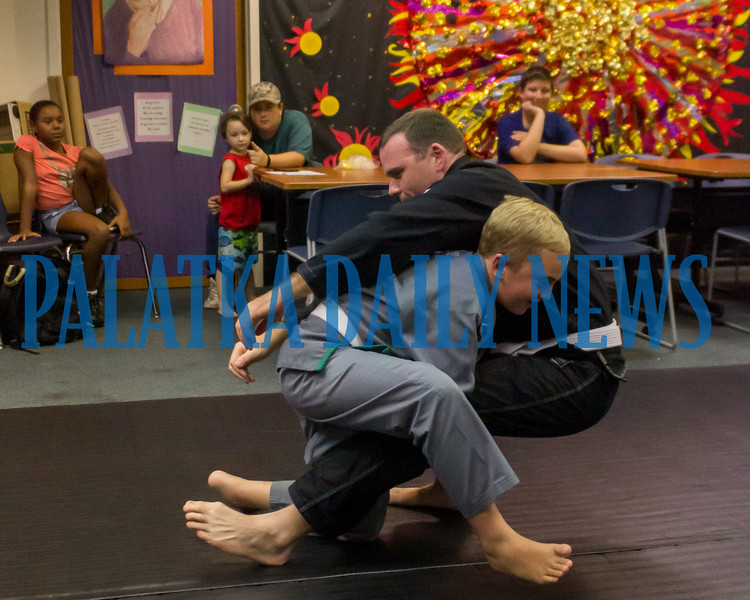 Eleven-year-old jiu jitsu student Peirce Browning demonstrates how he takes down Joe Theobold who is twice his size during a presentation at the Palatka Library on Friday afternoon. Fran Ruchalski/Palatka Daily News