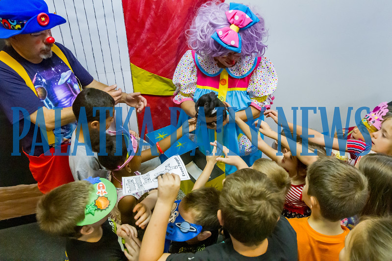 Children reach out to pet the bunny held by Pinky the Clown while her partner, Groovy, stands by at Toddler Fest at the Putnam County Headquarters Library on Saturday morning. About 700 people attended the second annual event this year. Fran Ruchalski/Palatka Daily News