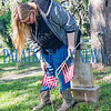 Crescent City High School senior Cora Finan, 18, plants a flag on a veteran's grave at the Eden Cemetery in Crescent City on Monday morning. Flags will be placed on veterans' graves in several cemeteries throughout the week to prepare for Memorial Day. Fran Ruchalski/Palatka Daily News