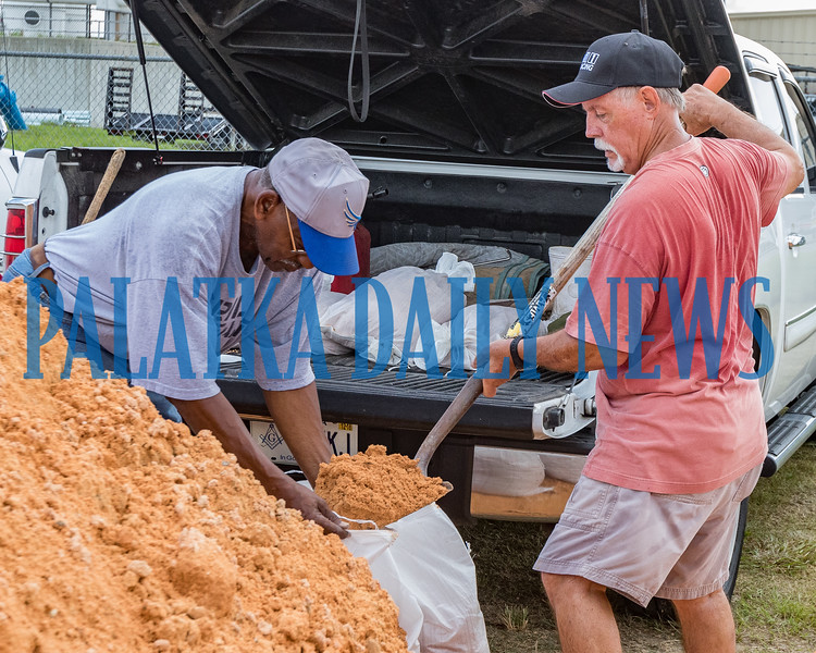 Clarence Hughes, left, holds a sandbag while Rick Wellborn fills it with dirt at the Putnam County Public Works complex in East Palatka Friday morning in advance of Hurricane Dorian's approach. Fran Ruchalski/Palatka Daily News