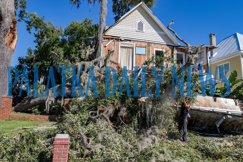 Duane Doty of Timberfalls Tree Service works on cutting the fallen branch that destroyed the front of the house at 418 River Street Monday afternoon. Timberfalls is donating the clean-up effort to help the homeowner. Fran Ruchalski/Palatka Daily News