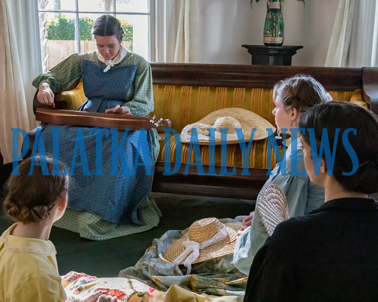 Some young ladies listen to music played on a dulcimer in the parlor of the Bronson-Mulholland House at Occupation Palatka on Saturday morning. Fran Ruchalski/Palatka Daily News