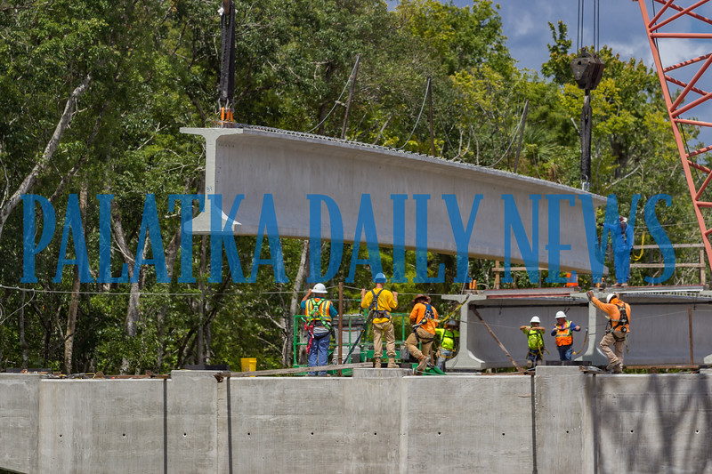 The overhead cranes maneuver the concrete I-beam over the new SR 17 bridge spanning Dunn's Creek while a crew waits to secure it in place. Fran Ruchalski/Palatka Daily News