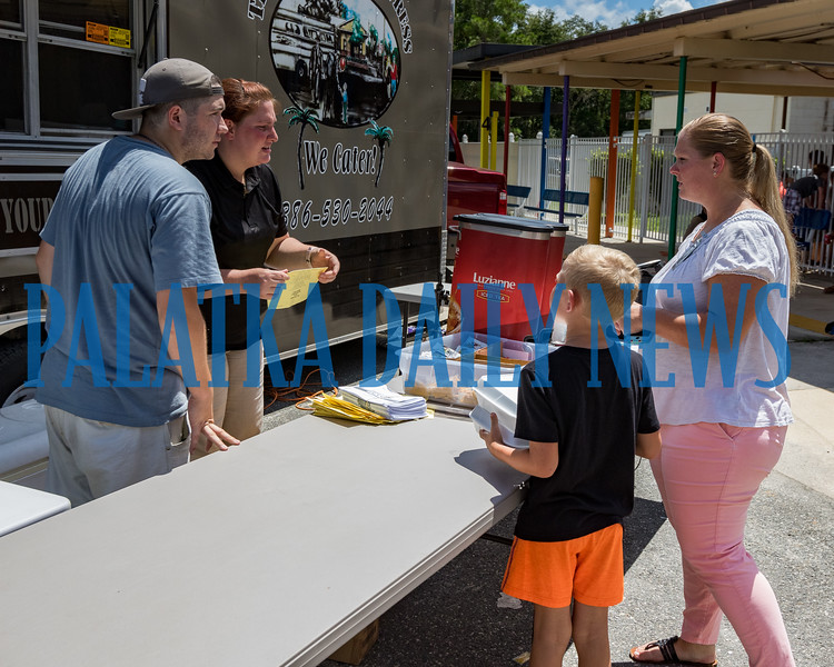 Jayson Yoas, left, and Andrea Bragg of the This and That food truck serve Lisa Wisham and her son Jason Wisham their lunch at Kelley Smith Elementary School on Wednesday at lunch time. Fran Ruchalski/Palatka Daily News