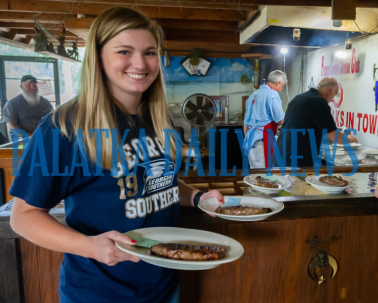 Payton Pellicer takes a pair of freshly-grilled steaks that her dad, Walton Pellicer just took off the grill to hungry diners at the Putnam County Shrine Club on Friday night. Fran Ruchalski/Palatka Daily News
