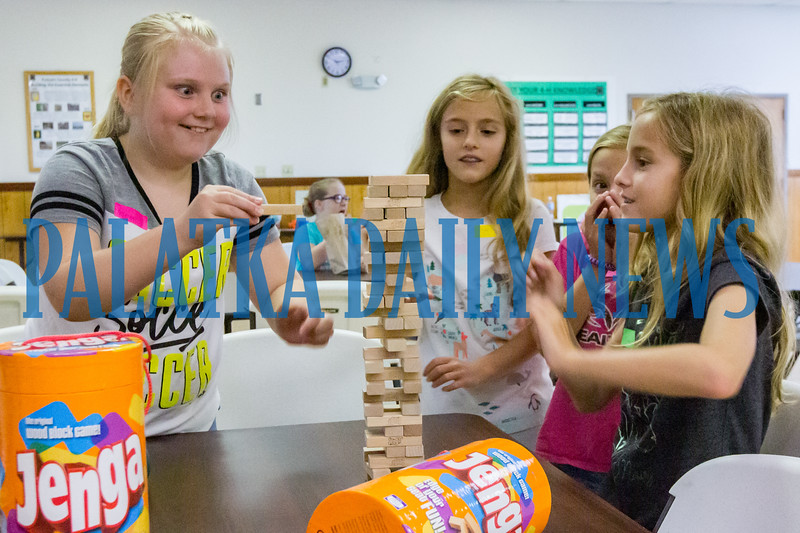 Makenna Harrell, 9, left, makes a risky move in a game of Jenga as Harley Strickland, 9, Lucille Strickland, 9, and Peyton Strickland, 9, are a bit nervous about the outcome at the 4H Fit 4 Life day camp. Fran Ruchalski/Palatka Daily News