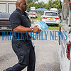 Police Chief Jason Shaw carries one of the many cases of water donated for the Bahamas to the police trailer. Fran Ruchalski/Palatka Daily News